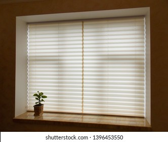 Pleated blinds XL Coulisse, beige color, with 50mm fold closeup in the window opening in the interior. Home blinds - modern bottom up privacy shades on apartment windows.
