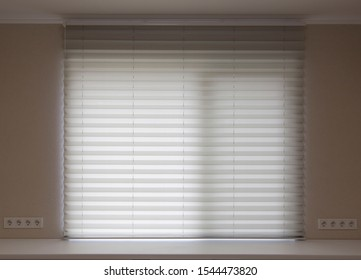 Pleated blinds XL Coulisse, beige color, with 50mm fold close up in the window opening in the interior. Luxury sun protection and window decoration. Modern shades.