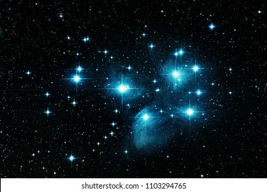 Pleiades stars in space with diffraction spikes and blue gases surrounding them