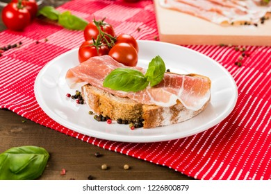 Plentiful table with bread, ham, white wine, tomatoes and ingredients