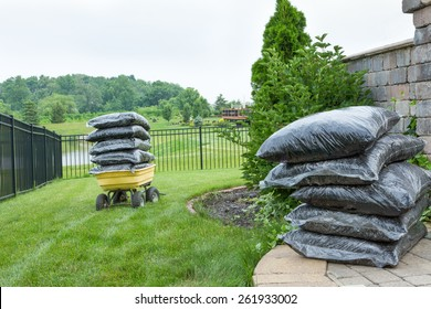 Plenty Bagged Mulches on Top of the Table and Garden Wagon, Preparation for Backyard Mulching