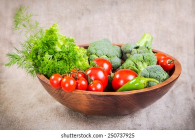 Plenty of colorful vegetables in wooden plate on linen background;