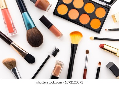 Plenty of makeup on the white table with eyelash brush, eye shadow, lipstick.