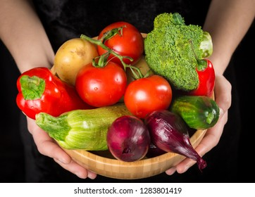 Plenty of vegetables in wooden dish on woman hands on black background
