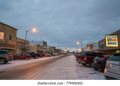 PLENTYWOOD, MONTANA - DECEMBER 5, 2017:  View looking down Main Street in Plentywood, Montana on an early December evening.  Fresh snow and ice on the roadway.