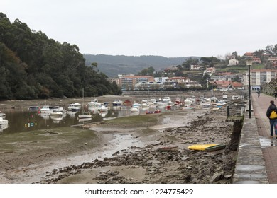 Plentzia, Spain - December 09, 2017: The ria hore of Plentzia, in the Basque Country, Spain, during a cold cloudy winter day, with low tide and small private boats on the mud