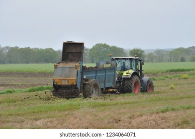PLERIN, FRANCE 27 MARCH, 2018: Tractor spreading manure on a field