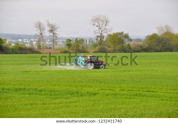 PLERIN, FRANCE 28 MARCH, 2018: Pesticide spraying by  tractor on a cereal field