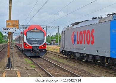PLESZEW, POLAND - JUNE 23, 2016 - Modernized EN57 electric train, operated by Koleje Wielkopolskie, passing a Lotos Kolej freight train transporting petrol at Pleszew station