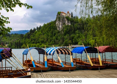 Pletna boats on Lake Bled with St. Marys Church of Assumption on small island in the middle of the lake. Bled, Slovenia, Europe. Mountains and valley on background. European nature and culture