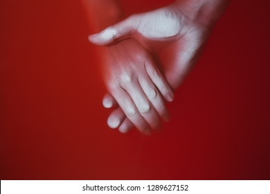 Plexus of the hands of a man and a woman in colored red bloody water, concept drama in relationships and betrayal, cover of a detective novel