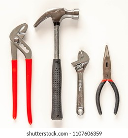 Pliers, needle nose pliers, hammer and an adjustable wrench isolated on white background. Top view.