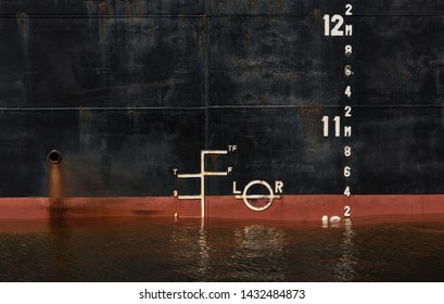 Plimsoll at the side of a bulk carrier in port. When a ship is being loaded, the water level must not exceed the line. This line is also called Load Line or Plimsoll Line.