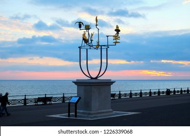 Artist's plinth on Hove seafront promenade, Brighton, UK, with a delicate metal constellation sculpture on it behind is the promenade nd the sea at sunset, the sky is red and blue from the setting sun