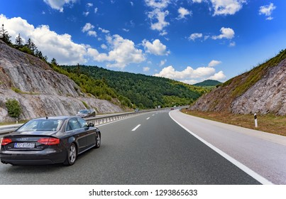 PLITVICE, CROATIA - JULY 16, 2017: Audi A4 moving on highway among mountain scenery in Plitvice, Croatia.