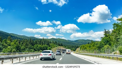 PLITVICE, CROATIA - JULY 16, 2017: Cars moving on highway among mountain scenery in Plitvice, Croatia.