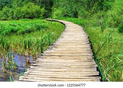 PLITVICE LAKES, CROATIA - 29 JUNE 2017. Wooden bridge across the lake in Plitvice Lakes.