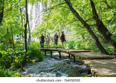 PLITVICE,CROATIA-JUNE 3,2017:people on the classic wooden path over the  water in the national park of plitvice lakes in croatia on a sunny day