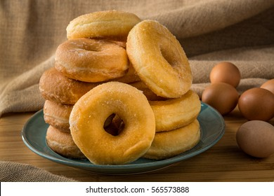 plle off fresh donuts in a plate with some eggs on background