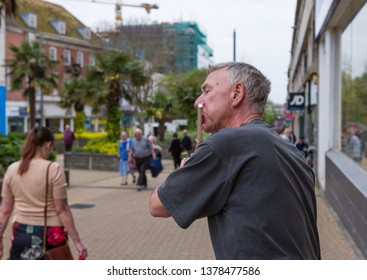 Plmyouth UK. 23/4/19:  A man entertains passers busking on a flute on a typical British high street.