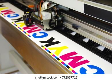 Plotter head printing CMYK test on white paper. Digital large inkjet machine working.