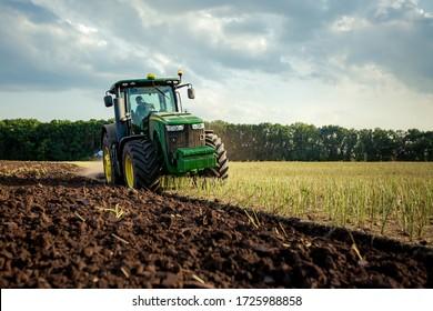 Ploughing a field with John Deere tractor. John Deere 8100 was manufactured in 1995-1999. Chernivtsi Oblast, Ukraine - July 22th, 2017