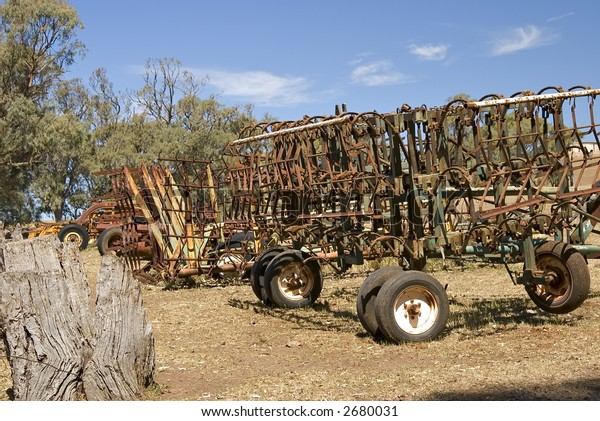 ploughs and farm machinery in a row