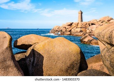 The Ploumanac'h lighthouse, named Mean Ruz, on the Pink Granite Coast in northern Brittany on the municipality of Perros-Guirec, France, with large pink granite rocks in the foreground.