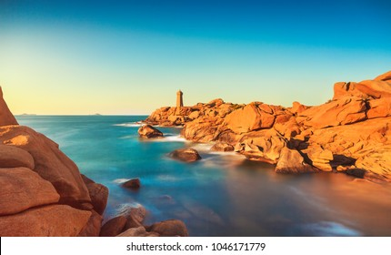 Ploumanach Mean Ruz lighthouse red sunset in pink granite coast, Perros Guirec, Brittany, France. Long exposure.