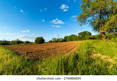Plowed field in the countryside. Prepared for sowing. Food production. A farm in Germany. Chimney on the horizon. Industry and agriculture. Blue sky.