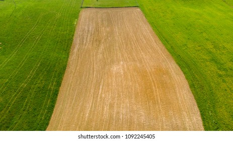 a plowed field of land surrounded by green
