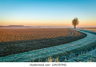 Plowed field next to a curved ditch in low sunlight in the winter season. The photo was taken in a Dutch polder near the village of Hank, North Brabant.