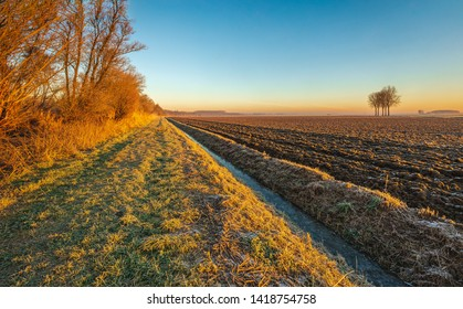 Plowed field next to a long and straight ditch in low sunlight in the winter season. The photo was taken in a Dutch polder near the village of Hank, North Brabant. It was early in the morning.