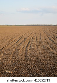 Plowed field on a background of blue sky in early spring
