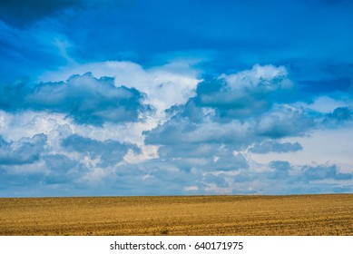 Plowed Field under Blue Sky with Clouds