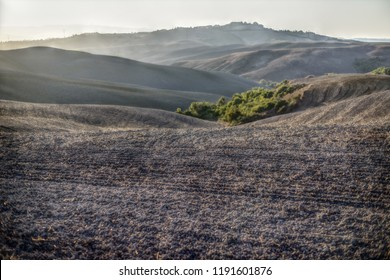 the plowed fields and a view of the hills and the countryside near Volterra, Tuscany, Italy