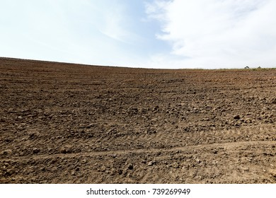 Plowed land ready for planting with sky taken by white clouds