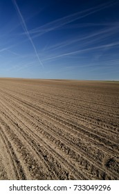 Plowed pattern on the brown field with blue sky