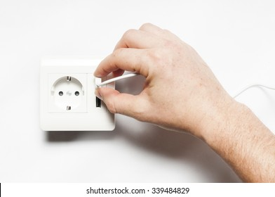 Plug in. A man inserts the usb plug into the usb port of power socket.