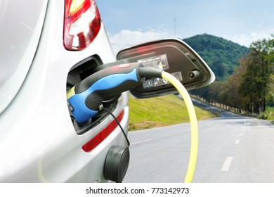 plug of power cable electric supply during charging at ev car (electric vehicle charging) on sky and road background