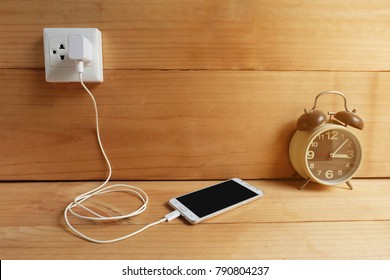 Plug in power outlet Adapter cord charger of mobile phone on wooden floor