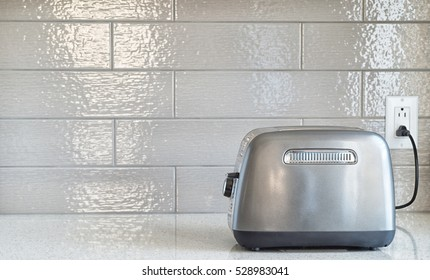 Plugged in retro styled toaster with sliced bread against grey ceramic backsplash in background