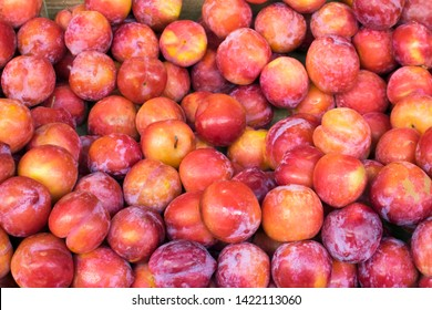 Plum background. Red fresh ripe plums placed on table in market. Organic red plums fruit in local farmers market.