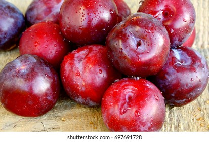 Plum Benefits Your Digestion & Cardiovascular Health. Many Plums(German name is Pflaumen dunkel )on wooden background.