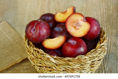 Plum Benefits Your Digestion & Cardiovascular Health. Many Plums(German name is Pflaumen dunkel ) in basket on wooden background.