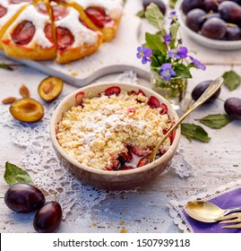 Plum Crumble, stewed plums topped with crumble of flour, butter and sugar  in a baking dish on a wooden table. Homemade fruit dessert