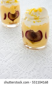 Plum Dessert Trifle in two Glasses on white lace fabric background with copy space.