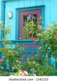 Plum door on teal blue house with roses