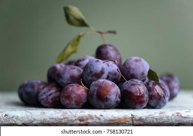 Plum. Fresh plum. Harvest. Autumn harvest. Autumn. Blue plums. Fresh plums on a wooden surface. Fresh plums on wooden table background. Слива. Урожай.