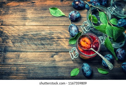 Plum fruit marmalade on rustic wooden background. Vintage style toned picture
